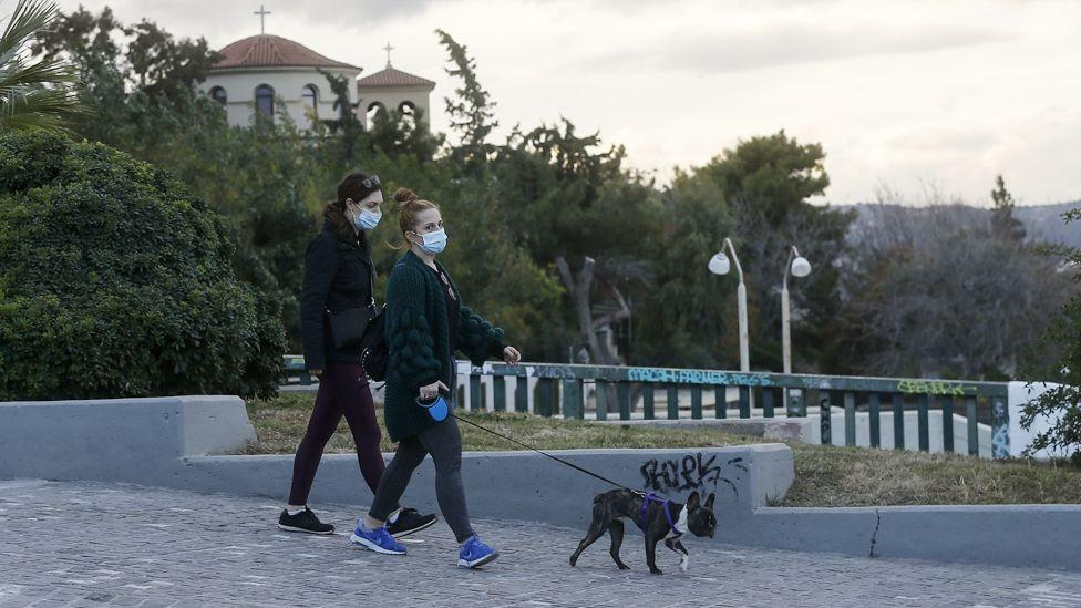 Афин хотын гудамжаар нохойгоо салхилуулахдаа ч амны хаалт зүүсэн харагдана.