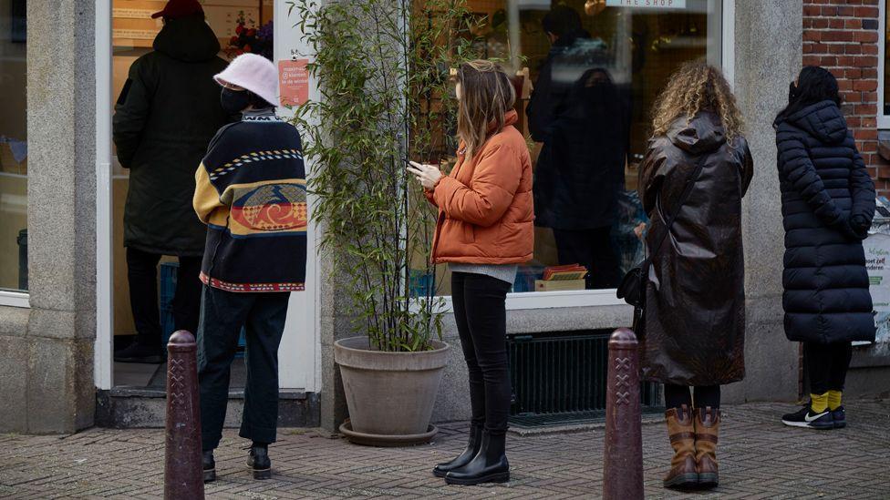 Ээлжээ хүлээн дараалан зогсож буй Амстердам хотын оршин суугчид.